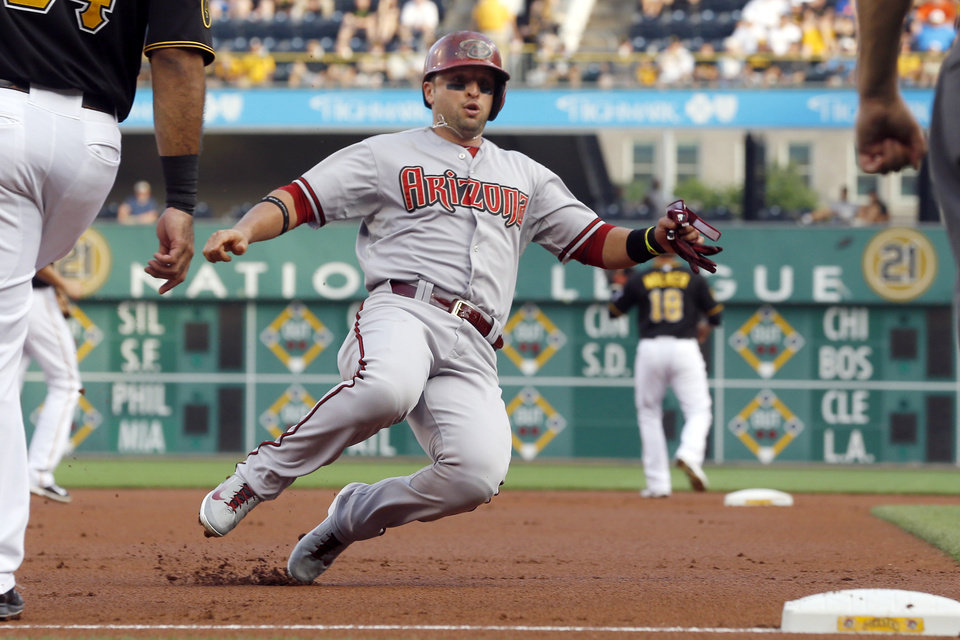 Photo - Arizona Diamondbacks' Martin Prado, left, takes third from first on a hit by Paul Goldschmidt as Pittsburgh Pirates second baseman Neil Walker (18) waits for the relay throw at second in the first inning of the baseball game on Tuesday, July 1, 2014, in Pittsburgh. (AP Photo/Keith Srakocic)