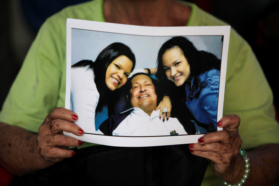 FILE - In this Feb. 15, 2013 file photo, a woman holds a newly purchased copy of a photo released by the government, showing Venezuela\'s President Hugo Chavez with two of his daughters, in Caracas,Venezuela. After more than eight years covering Venezuela, AP reporter Ian James finishes his assignment believing Venezuela\'s many long-term challenges, such as crime, corruption, a troubled economy and bitter political divisions, can seem as vast as the sea of crude oil that Venezuela sits atop. And with Chavez battling cancer, the country could be headed for big political shifts and possible turmoil. But James takes the view that the country\'s problems can be solved. (AP Photo/Fernando Llano, File)