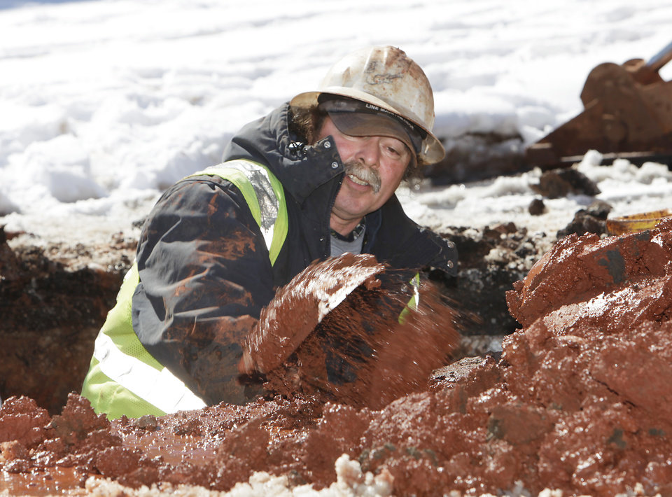 Photo - An Oklahoma City utility worker, who wished not to be identified, digs out a water line that burst due to the cold weather at 26th and north Harvey, February 10 , 2011.  Photo by David McDaniel, The Oklahoman