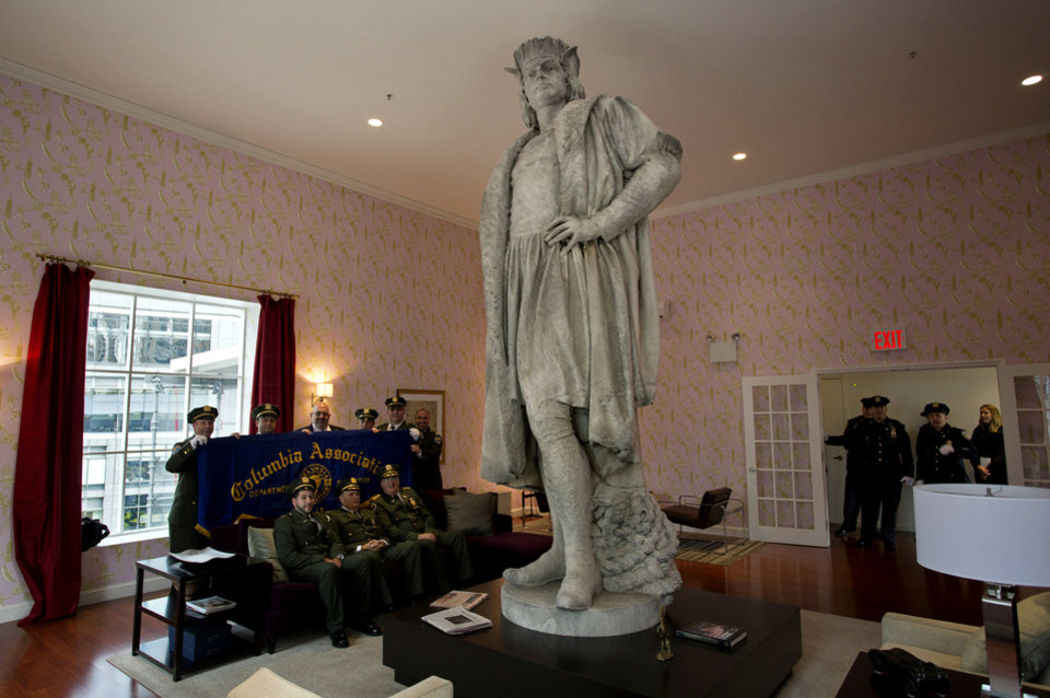 "Leaders of the Italian-American community and civil servants from New York, including police and sanitation workers and other guests, pose for pictures and also arrive in what is known as the living room created by artist Tatzu Nishi that surrounds Gaetano Russo's 1892 sculpture of Christopher Columbus 75 Feet Above Columbus Circle Sunday, Oct. 7, 2012, in New York. The art installation ""Tatzu Nishi: Discovering Columbus,"" which brings people to eye level with the Columbus statue, became part of an annual wreath laying ceremony that celebrates Columbus Day. (AP Photo/Craig Ruttle)"
