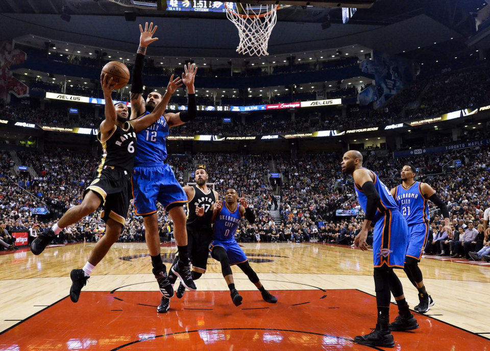 Photo - Toronto Raptors guard Cory Joseph (6) drives to the net against Oklahoma City Thunder center Steven Adams (12) during the first half of an NBA basketball game Thursday, March 16, 2017, in Toronto. (Nathan Denette/The Canadian Press via AP)