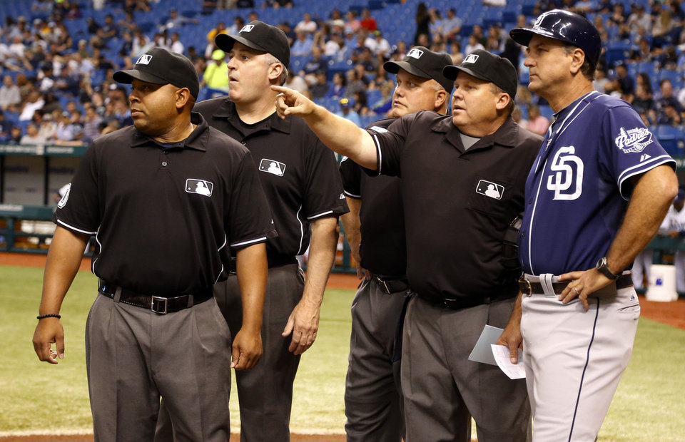 Photo - Umpires, from left, Adrian Johnson, Bill Welke, Brian O'Nora and Fieldin Culbreth meet with San Diego Padres third base coach Glenn Hoffman before an interleague baseball game against the Tampa Bay Rays, Friday, May 10, 2013, in St. Petersburg, Fla. (AP Photo/Mike Carlson)