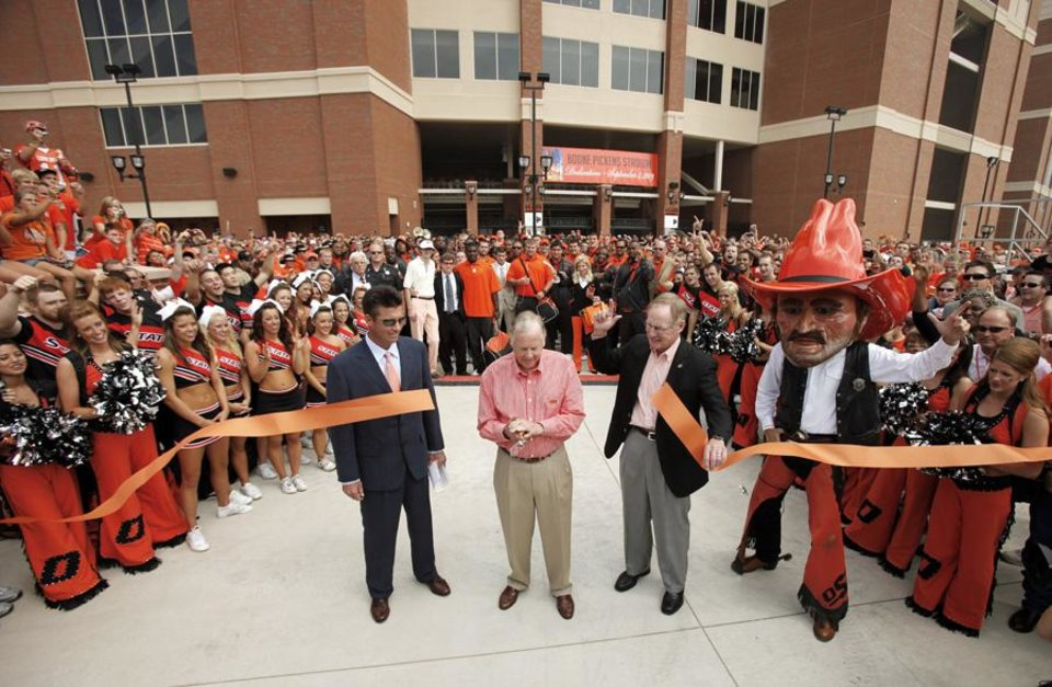 Photo -  OSU coach Mike Gundy and OSU president Burns Hargis watch as Boone Pickens cuts the ribbon to officially open the new stadium before the college football game between OSU and the University of Georgia at Boone Pickens Stadium on the campus of Oklahoma State University in Stillwater Saturday, Sept. 5, 2009. Photo by Doug Hoke, The Oklahoman. ORG XMIT: KOD