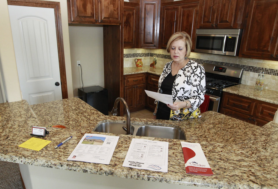 Photo -   In this Friday, Sept. 21, 2012, photo, Realtor Kimi George is pictured in the kitchen of a home for sale in Oklahoma City. Average U.S. rates on fixed mortgages fell again to new record lows. The decline suggests the Federal Reserve's stimulus efforts may be having an impact on mortgage rates. Mortgage buyer Freddie Mac said Thursday, Sept. 27, 2012, the rate on the 30-year loan dropped to 3.40 percent. That's down from last week's rate of 3.49 percent, which was the lowest since long-term mortgages began in the 1950s. (AP Photo/Sue Ogrocki)