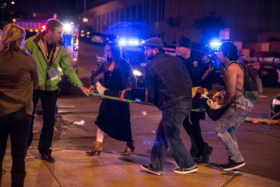 Photo - Bystanders assist first responders at the scene at SXSW festival in Austin, TX early Thursday morning March 13, 2014 where 2 people died and dozens more were injured after a hit and run. Police say a man and woman have been killed after a drunken driver fleeing from arrest crashed through barricades set up for the South By Southwest festival and struck the pair and others on a crowded street. (AP Photo/Colin Kerrigan)