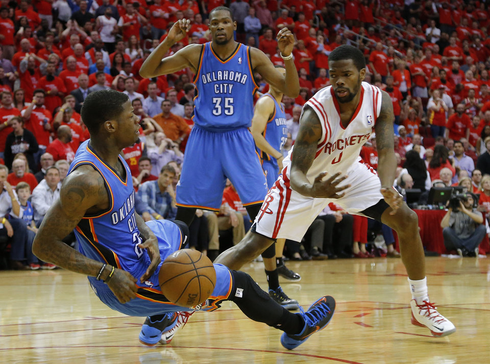 Photo - OKLAHOMA CITY THUNDER: Oklahoma City's DeAndre Liggins (25) falls to the floor as Houston's Aaron Brooks (0), and Oklahoma City's Kevin Durant (35) watch during Game 4 in the first round of the NBA playoffs between the Oklahoma City Thunder and the Houston Rockets at the Toyota Center in Houston, Texas, Monday, April 29, 2013. Oklahoma City lost 105-103. Photo by Bryan Terry, The Oklahoman