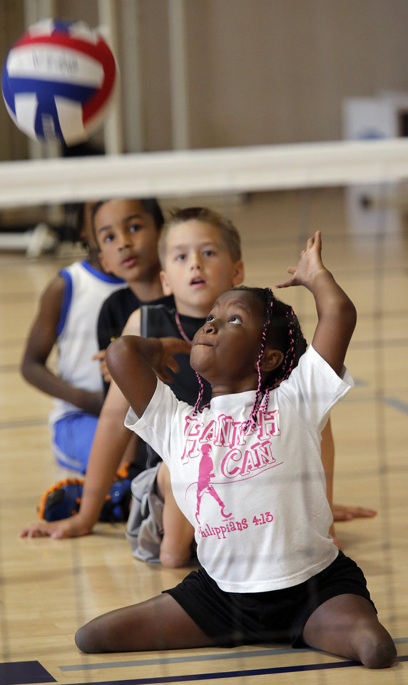 Hannah Hewett, 9, of Oklahoma, takes part in the sitting volleyball clinic during the opening day of activities for the Endeavor Games at the University of Central Oklahoma on Thursday, June 6, 2013 in Edmond, Okla. Photo by Chris Landsberger, The Oklahoman