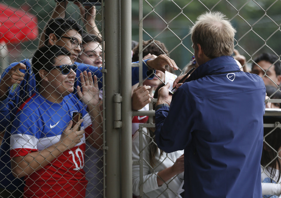 Photo - United States' head coach Juergen Klinsmann signs autographs at the Sao Paulo FC training center in Sao Paulo, Brazil, Wednesday, June 11, 2014. The U.S. will play in group G of the 2014 soccer World Cup. (AP Photo/Julio Cortez)
