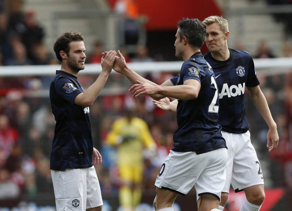 Photo - Manchester United's Juan Mata, left, celebrates his goal against Southampton with teammates during their English Premier League soccer match at St Mary's stadium, Southampton, England, Sunday, May 11, 2014. (AP Photo/Sang Tan)