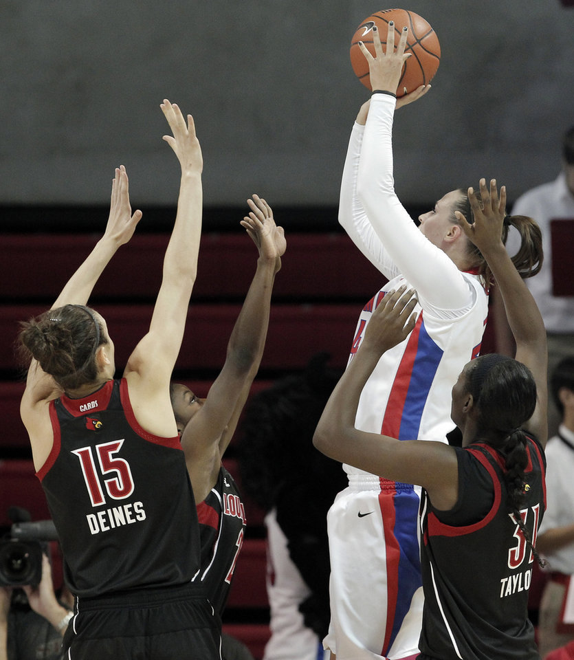 Photo - SMU guard Mallory Singleton, second from right, attempts to shoot as Louisville's Megan Deines (15), Asia Taylor (31) and Monny Niamke (2) defend in the first half of an NCAA college basketball game on Sunday, Jan. 19, 2014, in Dallas. (AP Photo/Brandon Wade)