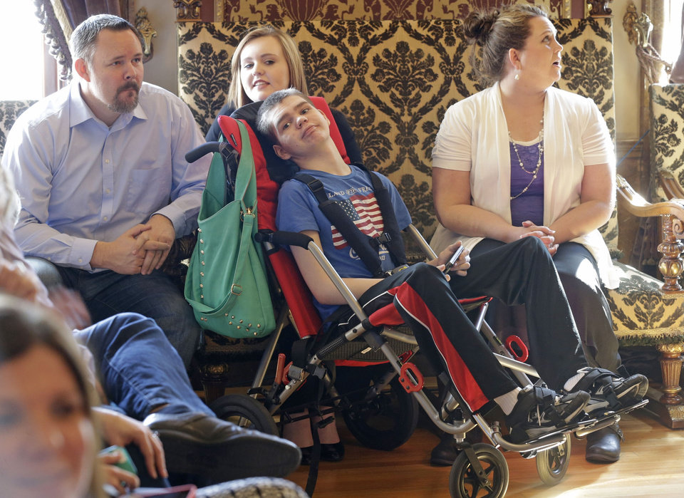 Photo - FILE - In this March 25, 2014, file photo, Stockton May, center, 12, waits with his sister Makayla, rear, and his mother Jennifer, right, before the H.B 105 bill signing ceremony at the Utah State Capitol, in Salt Lake City. Utah will begin issuing registration cards Tuesday, July 8, 2014, for its limited medical marijuana program targeting adults and children with severe epilepsy.  (AP Photo/Rick Bowmer, File)