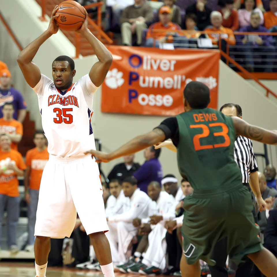 Photo - Clemson's Trevor Booker, left, looks to pass the ball while being defended by  Miami's James Dews during an NCAA college basketball game at Littlejohn Coliseum in Clemson, S.C. on Saturday, Feb. 13, 2010. Booker scored 18 points in the Tigers' 74-66 win over the Hurricanes. (AP Photo/Anderson Independent-Mail, Mark Crammer) ORG XMIT: SCAND106