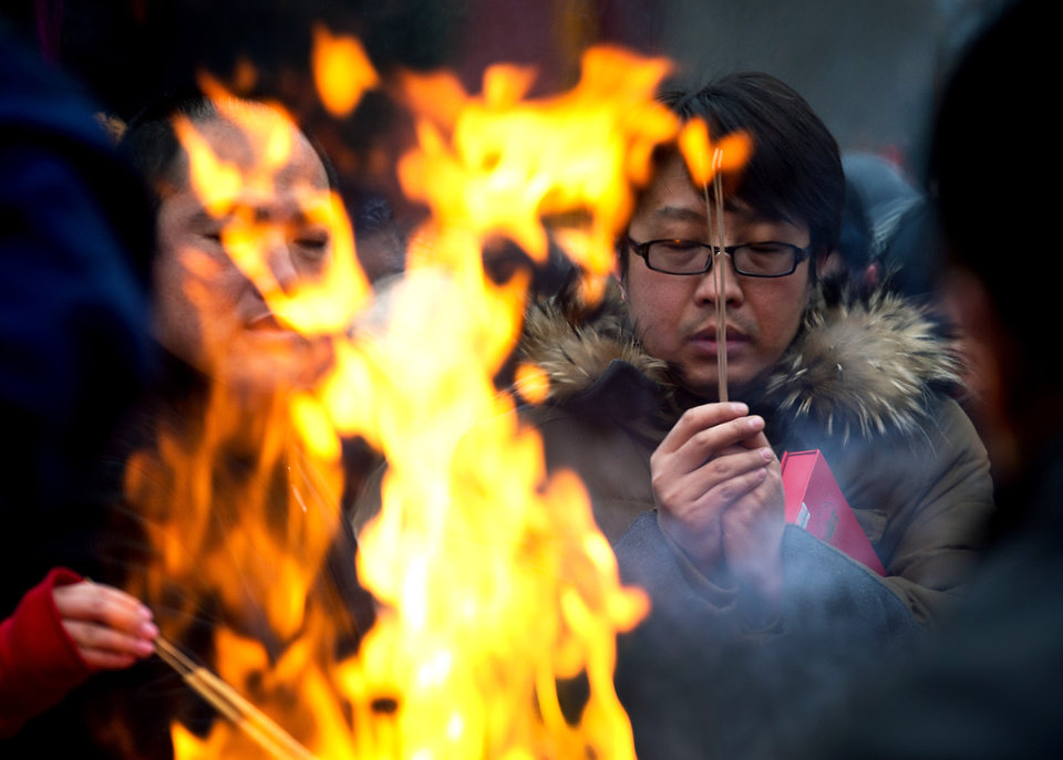 Photo - A Chinese man prays for health and fortune on the first day of the Lunar New Year at Yonghegong Lama Temple in Beijing Sunday, Feb. 10, 2013. Millions across China are celebrating the arrival of the Lunar New Year, the Year of the Snake, marked with a week-long Spring Festival holiday. (AP Photo/Andy Wong)