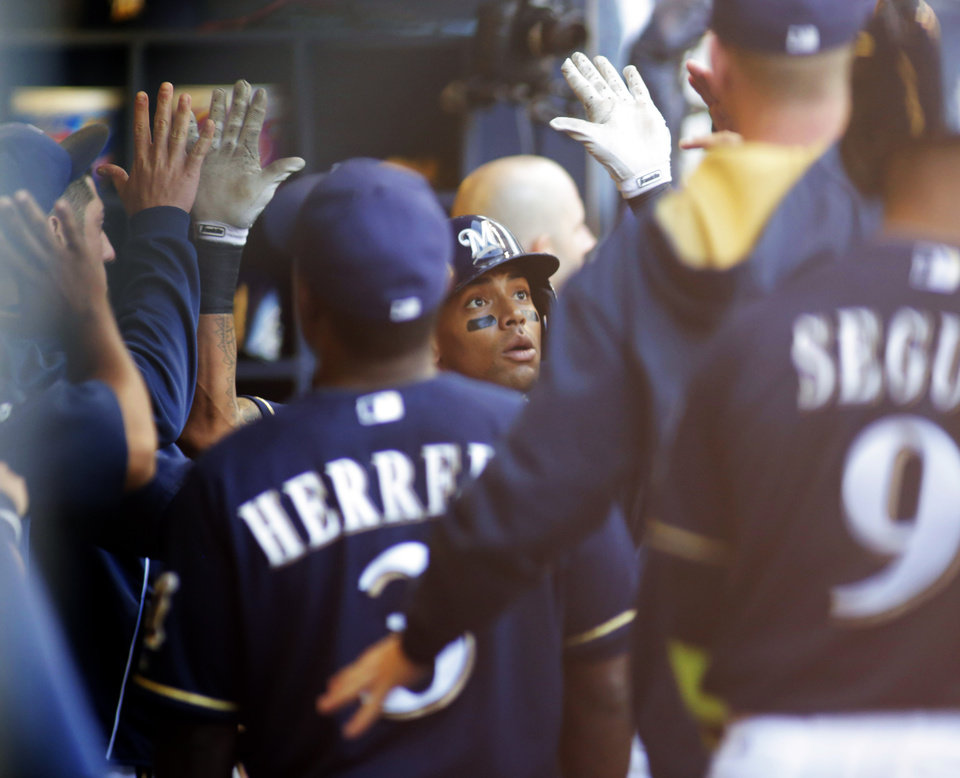 Photo - Milwaukee Brewers' Khris Davis, center, is congratulated by team mates after hitting a two run home run against the Los Angeles Dodgers during the second inning of a baseball game Saturday, Aug. 9, 2014, in Milwaukee. (AP Photo/Darren Hauck)