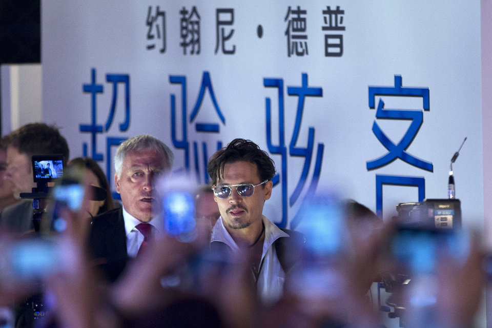 """Photo - Actor Johnny Depp, center, attends a promotional event for his new movie """"Transcendence"""" in Beijing, China, Monday, March 31, 2014. Johnny Depp showed off a diamond engagement ring that he called a """"chick's ring"""" on Monday, indirectly confirming rumors of his engagement to actress Amber Heard. (AP Photo/Alexander F. Yuan)"""