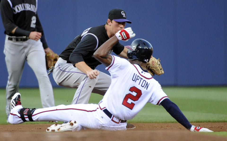 Photo - Atlanta Braves' B.J. Upton (2) safely slides into second base on a double as Colorado Rockies' DJ LeMahieu turns to try to tag him during the first inning of a baseball game Friday, May 23, 2014, in Atlanta. (AP Photo/David Tulis)