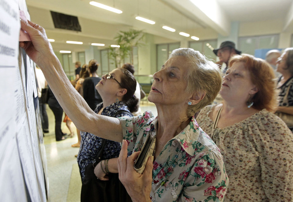 Photo -   Women check the list of candidates before voting in municipal elections in Sao Paulo, Brazil, Sunday, Oct. 7, 2012. Voters across Latin America's biggest country are electing mayors and municipal council members. (AP Photo/Andre Penner)