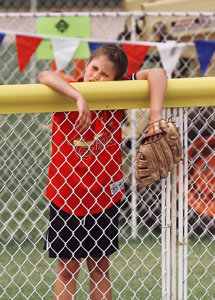 Photo - NCAA Women's College World Series. Waiting for a foul ball can be tiring as Tamara Brown, 9, of Sentinel, discovers Sunday afternoon as she leans against the outfield fence in left field during the game between UCLA and DePaul at Don Porter Hall of Fame Stadium in Oklahoma City. A few fouls ball came nearby, but the young softball player was never able to get the prized souvenir she sought. Photo by Jim Beckel, The Oklahoman Archive