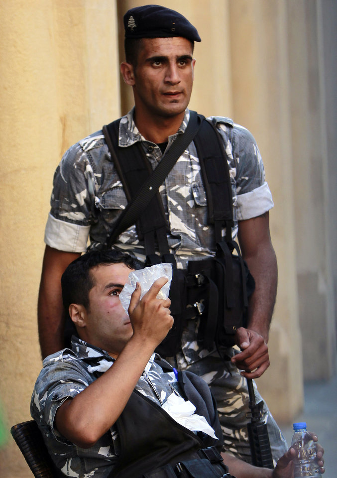 Photo - A wounded Lebanese riot police applys ice on his eye during clashes with protersters during a demonstration in Beirut, Lebanon, Thursday, June 20, 2013. Lebanon's parliament on May 29 extended its term by a year and a half, skipping scheduled elections because of the country's deteriorating security linked to the civil war next door in Syria. (AP Photo/Bilal Hussein)