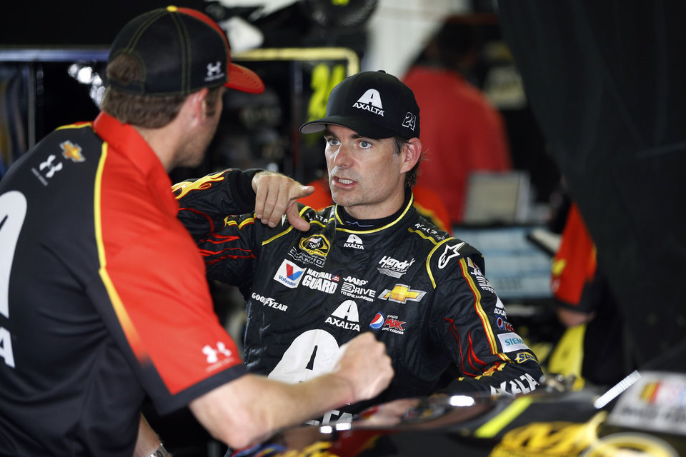 Photo - Jeff Gordon, right, talks with a crew member after a practice session for Sunday's NASCAR Sprint Cup Series auto race at Pocono Raceway, Saturday, Aug. 2, 2014, in Long Pond, Pa. (AP Photo/Matt Slocum)