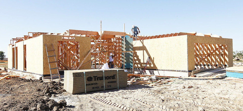 Photo - Workers build a house at 632 SW 6 in Moore.  PAUL B. SOUTHERLAND - The Oklahoman