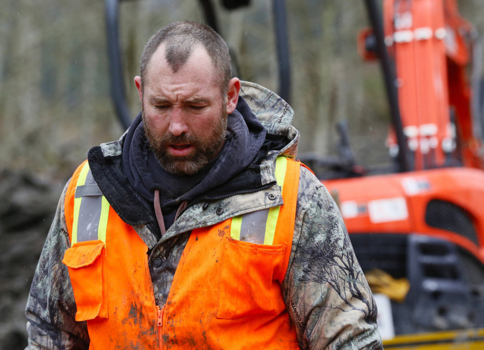 Photo - A weary searcher bows his head as he walks out of the west side of the mudslide site with a small saw on Highway 530 near mile marker 37  in Arlington, Wash., on Sunday, March 30, 2014. Periods of rain and wind have hampered efforts the past two days. (AP Photo/Rick Wilking, Pool)