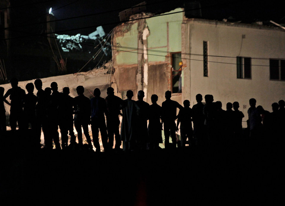 Photo - Bangladeshi men watch rescue operations at the site of a building that collapsed Wednesday in Savar, near Dhaka, Bangladesh, Friday, April 26, 2013. By Friday, the death toll reached at least 270 people as rescuers continued to search for injured and missing, after a huge section of an eight-story building that housed several garment factories splintered into a pile of concrete.(AP Photo/Kevin Frayer)
