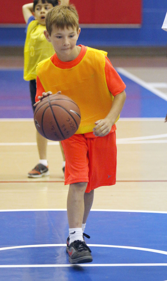 Photo -  Nicholas Capps, 8, practices dribbling and passing during summer sports camp on Monday at Oklahoma City Community College. Photo by Paul Hellstern, The Oklahoman   PAUL HELLSTERN -  Oklahoman
