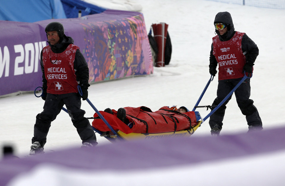 Photo - Italy's Omar Visintin is carried off the course in a stretcher after crashing in the second semifinal of the men's snowboard cross at the Rosa Khutor Extreme Park, at the 2014 Winter Olympics, Tuesday, Feb. 18, 2014, in Krasnaya Polyana, Russia. (AP Photo/Andy Wong)