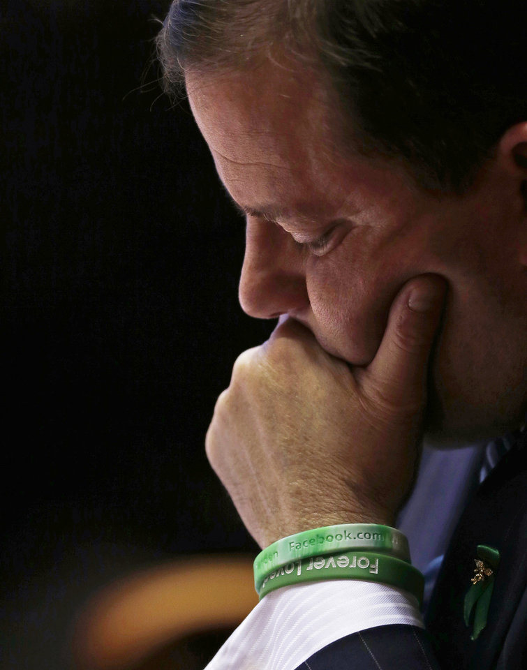 Photo - While wearing green wrist bands honoring the victims of the Newtown school shooting, Senate Minority Leader John McKinney, R-Fairfield, who represents Newtown, Conn., looks at his notes prior to addressing the Senate floor at the Capitol in Hartford, Conn., Wednesday, April 3, 2013. Hundreds of gun rights advocates are gathering at the statehouse in Hartford ahead of a vote in the General Assembly on proposed gun-control legislation. (AP Photo/Charles Krupa)