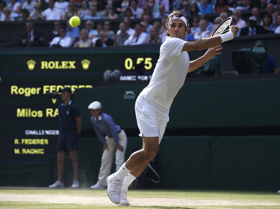 Photo - Roger Federer of Switzerland reaches out to play a return to Milos Raonic of Canada during their men's singles semifinal match at the All England Lawn Tennis Championships in Wimbledon, London, Friday, July 4, 2014. (AP Photo/Pavel Golovkin)