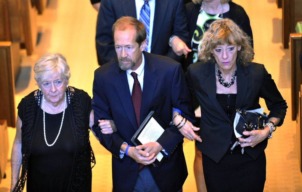 Elmore Leonard's son Chris Leonard, center, walks arm-in-arm with his mother Beverly Decker (Elmore's first wife) and his wife Suzy Leonard at the conclusion of his father's funeral mass inside Holy Name Church in Birmingham, Mich, Saturday Aug. 24, 2013/ The beloved Metro-Detroit crime novelist Elmore Leonard died Tuesday at his home in Bloomfield Village at age 87. (AP Photo/The Detroit News, John T. Greilick)