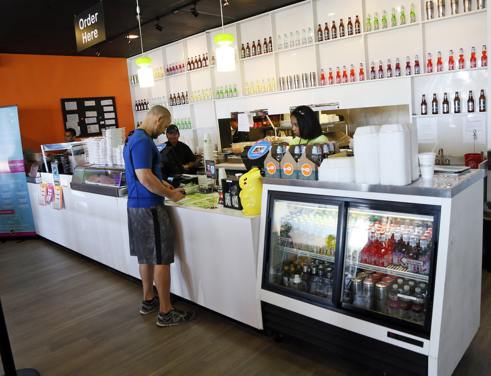 Photo -  A customer orders Wednesday at the counter of the Nhinja Sushi & Wok, 13905 N May Ave., in Oklahoma City.    NATE BILLINGS -