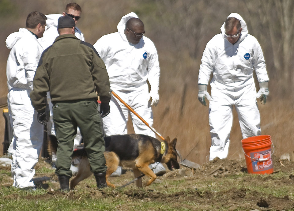 ADVANCE FOR SUNDAY, JAN. 27 - In this Thursday, April 12, 2012 photo, state police investigators pause to allow a dog to inspect dirt and debris at a dig site off Vermont 15 near Lang Farm in Essex, Vt., in what Essex Police Chief Brad LaRose described as part of the ongoing investigation into the disappearance of Bill and Lorraine Currier, who went missing June 2011.  After confessing to killing a 18-year old woman in Alaska, Israel Keyes is suspected of killing Bill and Lorraine Currier. Keyes was found dead in his cell on Dec. 2, 2012.   Investigators have used Keyes' financial and travel records to piece together a timeline of his whereabouts from Oct. 4, 2004, to March 13, 2012. He traveled throughout the United States and made short trips into Canada and Mexico. (AP photo by Ryan Mercer, Burlington Free Press) MAGS OUT; MANDATORY CREDIT; NO SALES; ONLINE OUT