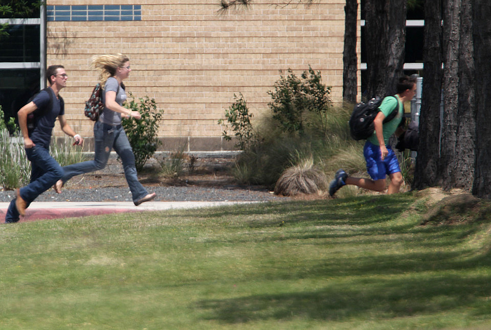 Photo - Students run from the Lone Star College's Cy-Fair campus in Cypress, Texas, where a student went on a building-to-building stabbing attack Tuesday, April 9, 2013. The attacker wounded at least 14 people before being subdued and arrested, authorities said.  (AP Photo/Houston Chronicle, James Nielsen) MANDATORY CREDIT