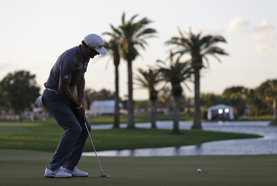 Photo - Dustin Johnson watches his putt on the 18th green during the second round of the Cadillac Championship golf tournament Friday, March 7, 2014, in Doral, Fla. Johnson bogeyed the hole. (AP Photo/Wilfredo Lee)