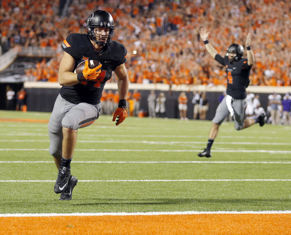 Photo - Oklahoma State's Jeremy Seaton (44) scores a touchdown as quarterback J.W. Walsh (4) celebrates in the fourth quarter during the college football game between the Oklahoma State Cowboys (OSU) and the Central Arkansas Bears at Boone Pickens Stadium in Stillwater, Okla., Saturday, Sept. 12, 2015. Photo by Sarah Phipps, The Oklahoman