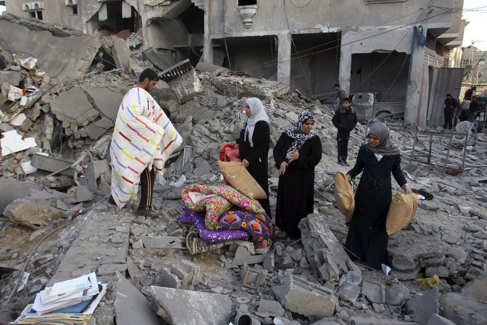 Palestinians collect their belongings from the rubble of the building of Attia Abu Inkara, a Hamas militant leader, following an Israeli air strike in Rafah refugee camp in southern Gaza Strip, Sunday, Nov. 18, 2012. An Israeli envoy held talks with Egyptian officials Sunday on a ceasefire in his country's offensive on Gaza as Israel widened the range of its targets, striking more than a dozen homes of Hamas militants and two media officials. (AP Photo/Eyad Baba)