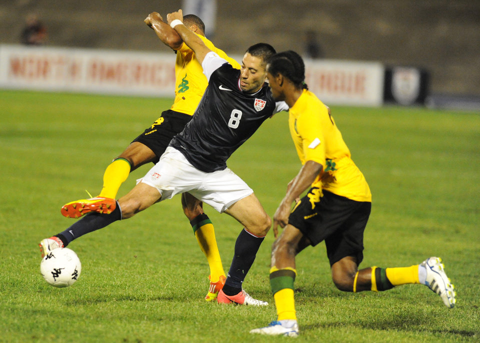 Photo -   United States' Clint Dempsey, center, fights for the ball with Jamaica's Jason Morrison, left, and Ryan Johnson during a 2014 World Cup qualifying soccer match in Kingston, Jamaica, Friday, Sept. 7, 2012. Jamaica won 2-1. (AP Photo/Collin Reid)