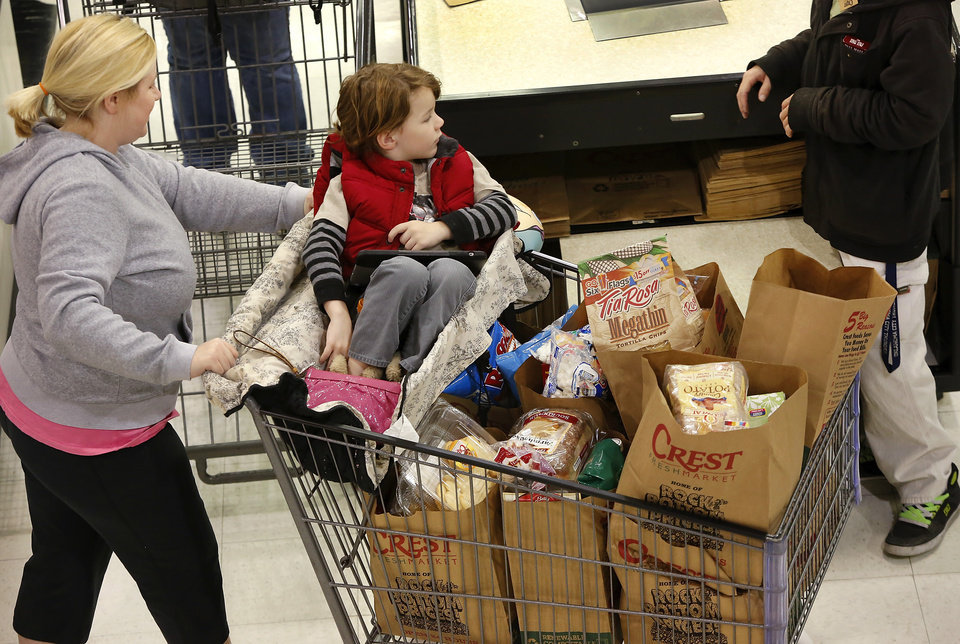 A woman pushes a full shopping cart away from the checkout line. The threat of a severe winter storm, expected to arrive in Oklahoma City on Christmas Day,  sent hundreds of shoppers scurrying in the aisles at Crest Foods, 15th and Santa Fe in Edmond Monday, Dec. 24, 2012, Photo by Jim Beckel, The Oklahoman