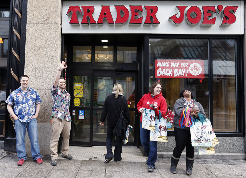 Photo - Employess greet people outside of Trader Joe's on Boylston Street in Boston, Wednesday, April 24, 2013, as businesses opened and traffic was allowed to flow all the way down Boylston Street for the first time since two explosions at the Boston Marathon on April 15. (AP Photo/Michael Dwyer)