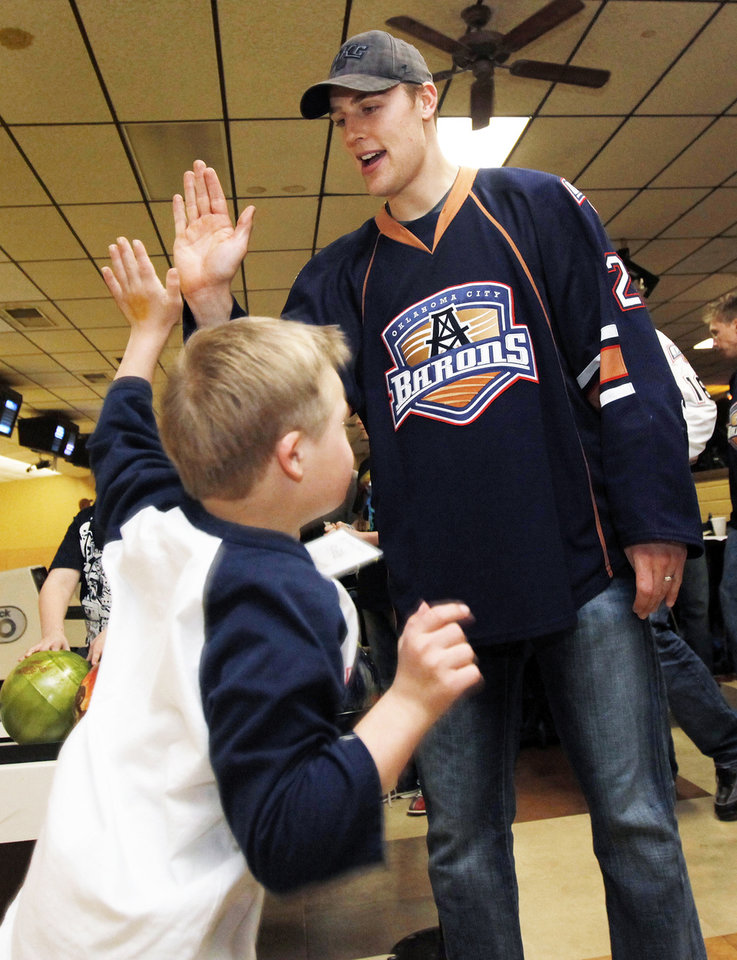 Photo - CHILD / CHILDREN / KIDS: Barons player Tanner House (21) gives Reis Wathen, 9, a high-five during the Barons Buddies event with the Oklahoma City Barons AHL hockey team and Special Olympians at AMF Sunny Lanes bowling alley in Del City, Okla., Wednesday, Jan. 25, 2012. Photo by Nate Billings, The Oklahoman