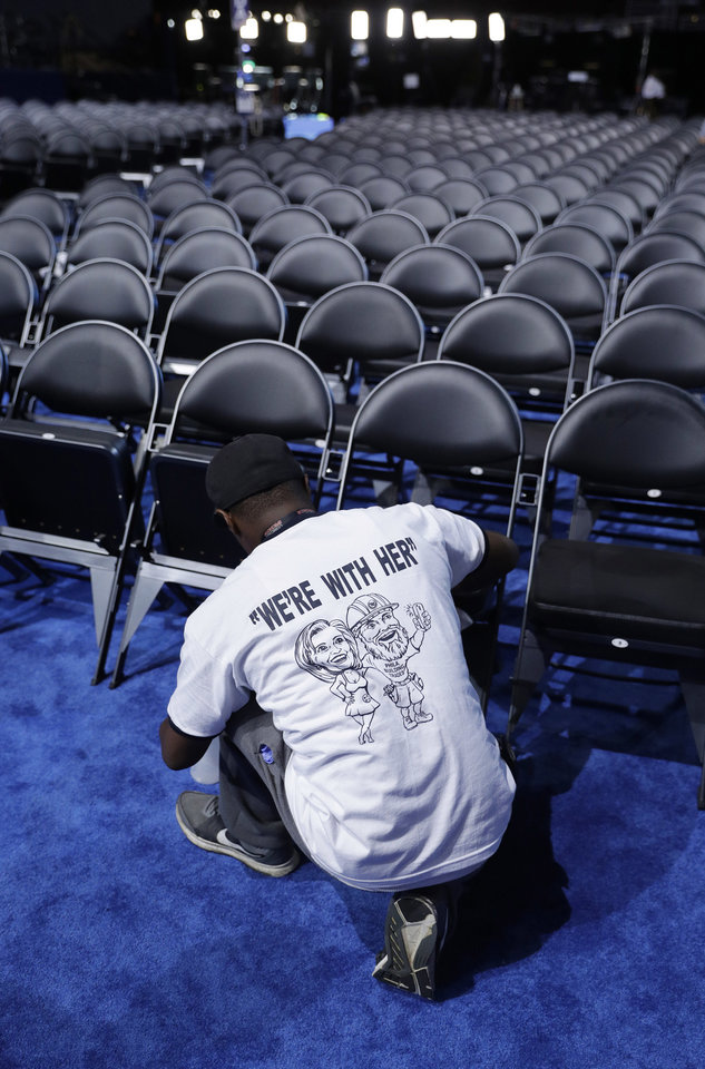 Photo - Timothy Dockens cleans chairs in the convention hall during preparations before the start of the 2016 Democratic Convention, Monday, July 25, 2016, in Philadelphia. (AP Photo/John Locher)