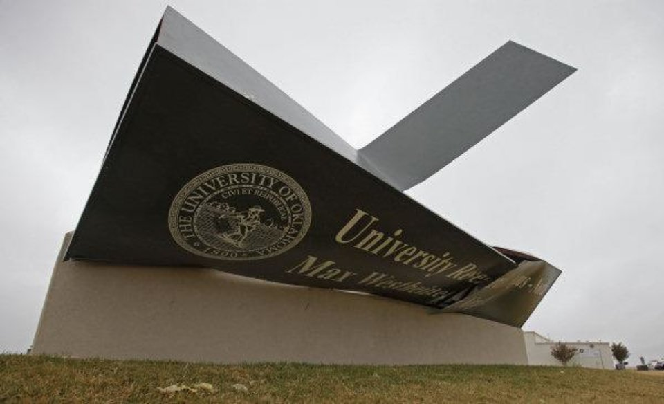 Photo - A wind damaged sign marks the entrance to at Max Westheimer Airport in Norman Tuesday. The entry sign was damaged after severe weather Monday night.  STEVE SISNEY - THE OKLAHOMAN