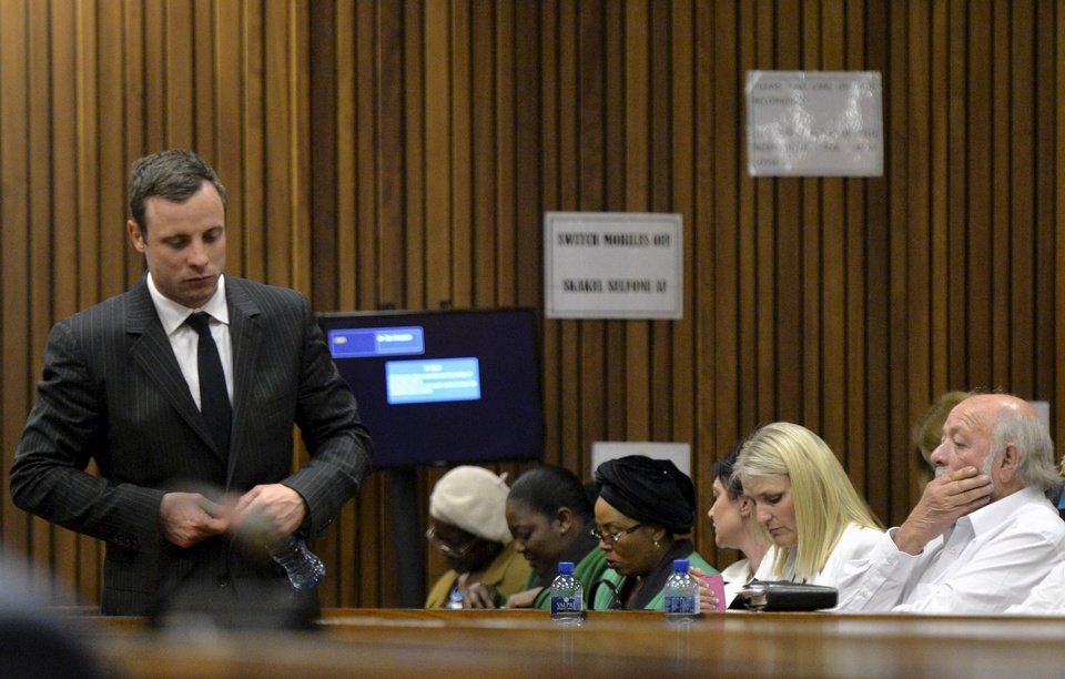 Photo - Oscar Pistorius, left, walks past Barry Steenkamp, the father of Reeva Steenkamp, right, during his trial, in Pretoria, South Africa, Friday, Aug. 8, 2014. The chief defense lawyer for Pistorius delivered final arguments in the athlete's   trial on Friday, alleging that Pistorius thought he was in danger when he killed girlfriend Reeva Steenkamp and also that police mishandled evidence at the house where the shooting happened. (AP Photo/ Herman Verwey, Pool)