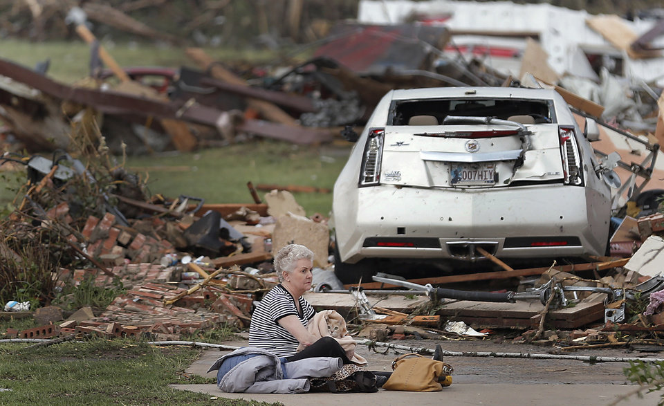 Photo - Kay James holds her cat as she sits in her driveway after her home was destroyed by the tornado that hit the area on Monday, May 20, 2013 in Oklahoma City, Okla. (AP Photo/The Oklahoman, Chris Landsberger)