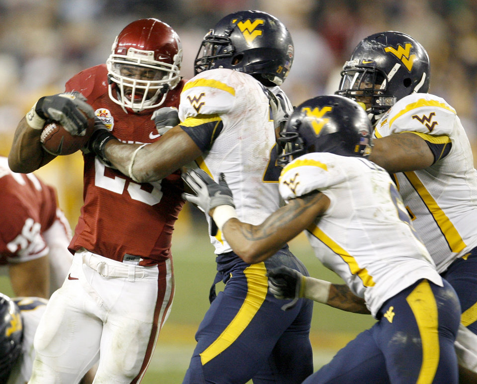 Photo - OU's Allen Patrick is brought down by a group of West Virginia defenders during the second half of the Fiesta Bowl college football game between the University of Oklahoma Sooners (OU) and the West Virginia University Mountaineers (WVU) at The University of Phoenix Stadium on Wednesday, Jan. 2, 2008, in Glendale, Ariz. 