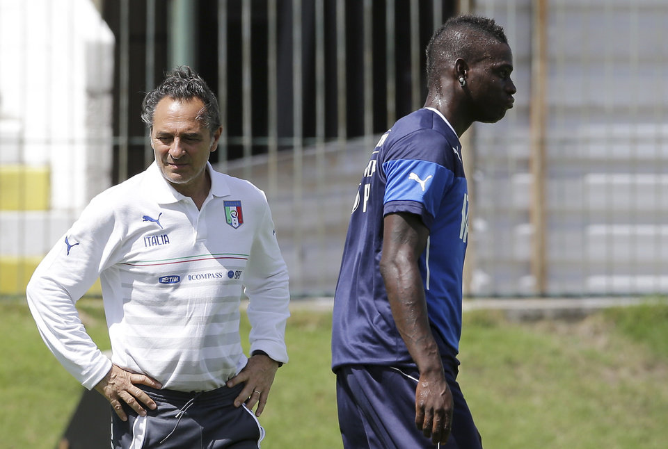 Photo - Italy coach Cesare Prandelli stands on the pitch as forward Mario Balotelli walks past during a training session at the Maria Lamas Farache stadium in Natal, Brazil, Sunday, June 22, 2014. Italy plays in group D of the Brazil 2014 soccer World Cup. (AP Photo/Antonio Calanni)