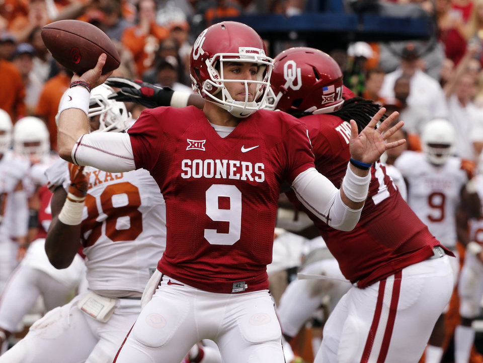 Photo - Oklahoma's Trevor Knight (9) throws during the second half of the Red River Showdown college football game between the University of Oklahoma Sooners (OU) and the University of Texas Longhorns (UT) at the Cotton Bowl in Dallas, Texas on Saturday, Oct. 11, 2014. 