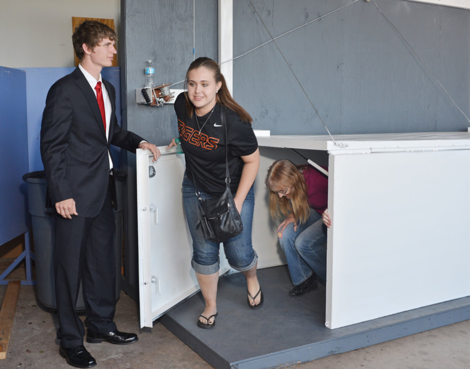 Photo -  Ryan Bernardy, left, a Crescent High School senior, opens the door of the Tornado Instashelter to allow Jordan Booth and Karen Nilson to leave the shelter. Photo by M. Tim Blake, For The Oklahoman   M. Tim Blake
